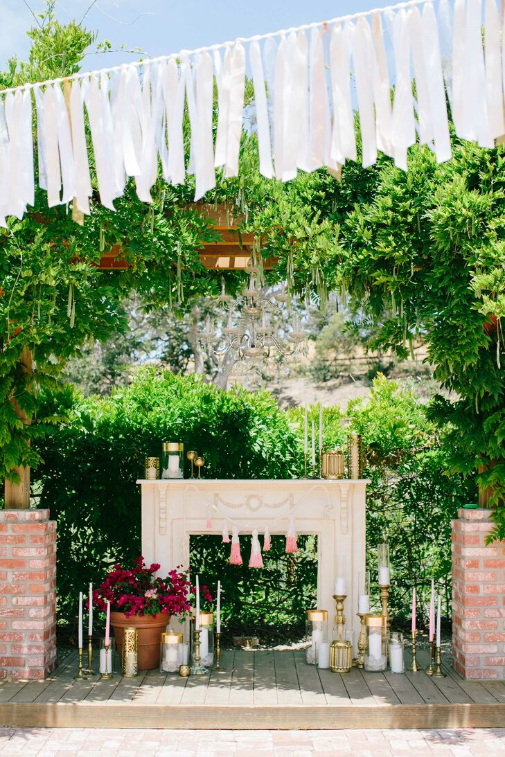 Surrounded by the lush landscaping at the Gardens at Peacock Farms in Arroyo Grande, California, Linsay and Stefan got married on the elevated wooden platform decorated with gold candles and an elegant mantel.