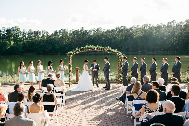 The calm waters and thick green forests of Angus Barn Lake provided the backdrop for Katharine and Nate's vows. Bunches of pastel blooms and a lush green garland gave the ceremony space a polished feel.