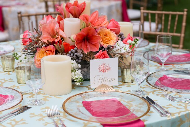 The reception tables were numbered with white stationery decorated with pink coral detailing and gold numbers written out. They were each displayed in gold-painted seashell holders to keep with the destination wedding feel.