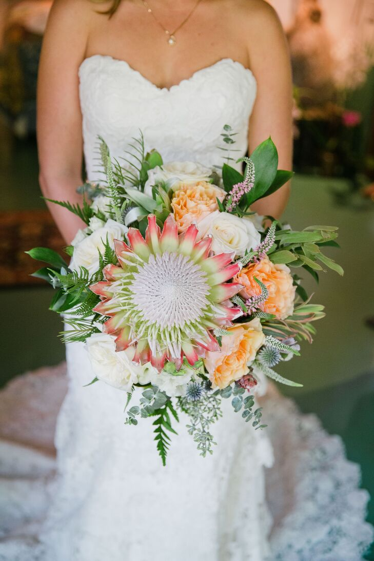 """The flowers were important to Mallory and Richie, and """"we believe they really stole the show."""" Her bouquet consisted of flowers from Northern California and South Africa, including a stunning king protea, candy-stripe leucadendron, heirloom garden roses, lisianthus, large-leaf dusty miller, grevillea, seeded eucalyptus, gomphrena, baby blue eucalyptus and passionflowers."""
