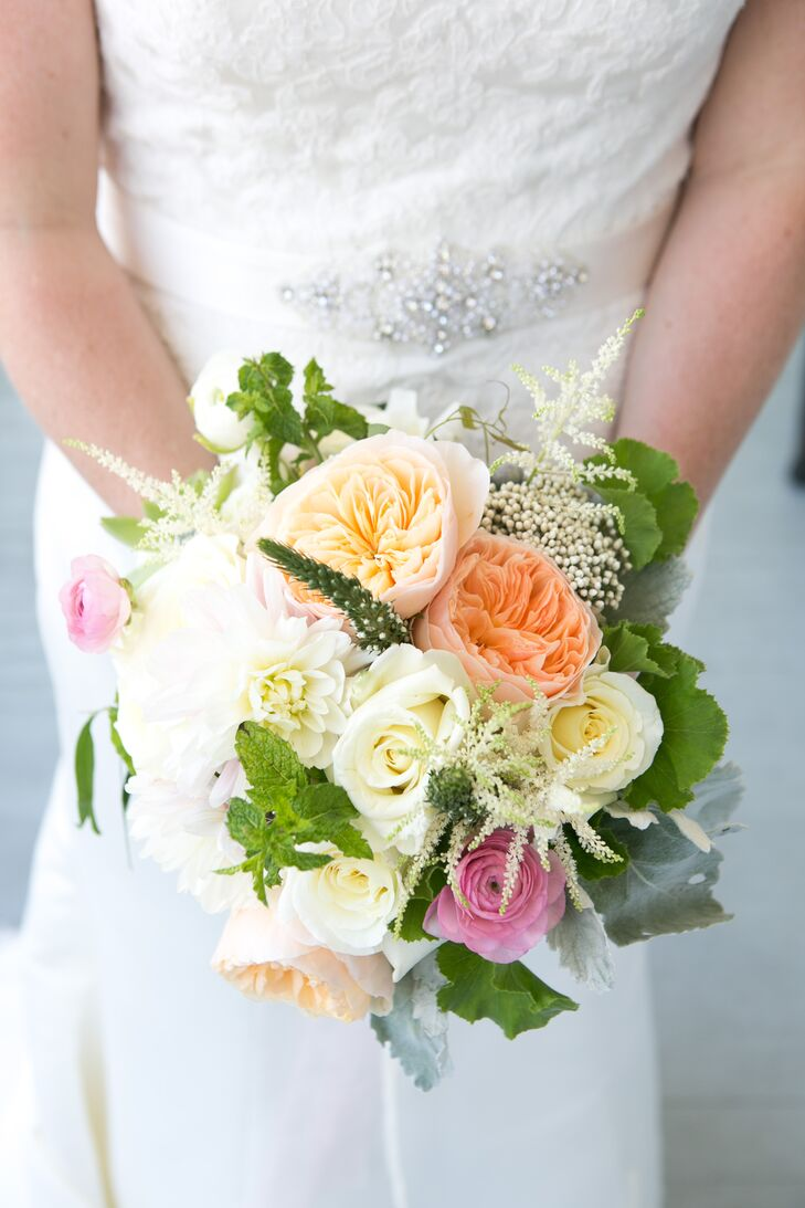 Inspired by Pinterest and a few other sites, Catherine worked with her florist to make a series of bright arrangements. To match her lace dress, Pink Dahlia Vintage designed a bright bouquet of peach and orange garden roses, white roses, pink ranunculus, dusty miller, greenery and lush white dahlias.