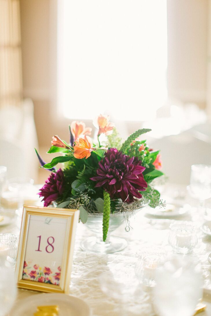 Dahlias and alstroemerias were the colorful focal points of the centerpieces. The table numbers were displaying in simple gold frames and were highlighted by a watercolor floral design.