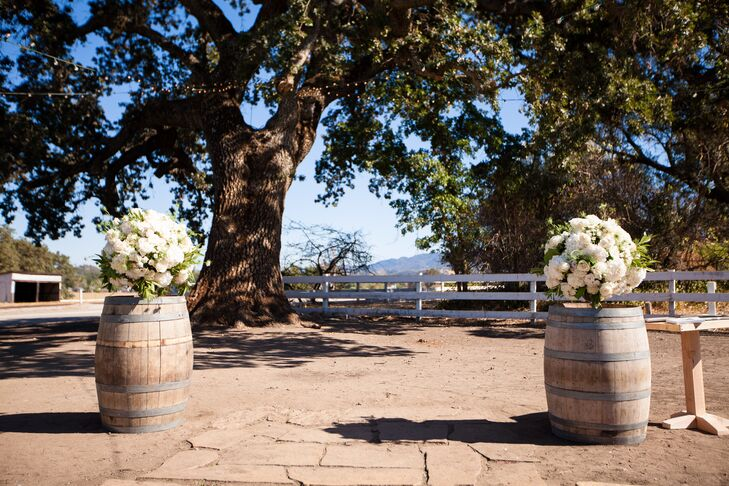Keviann and Ben were married on an elevated stone platform outside at Santa Margarita Ranch in Santa Margarita, California. They were married between two ivory hydrangea and rose arrangements positioned on top of wooden barrels.