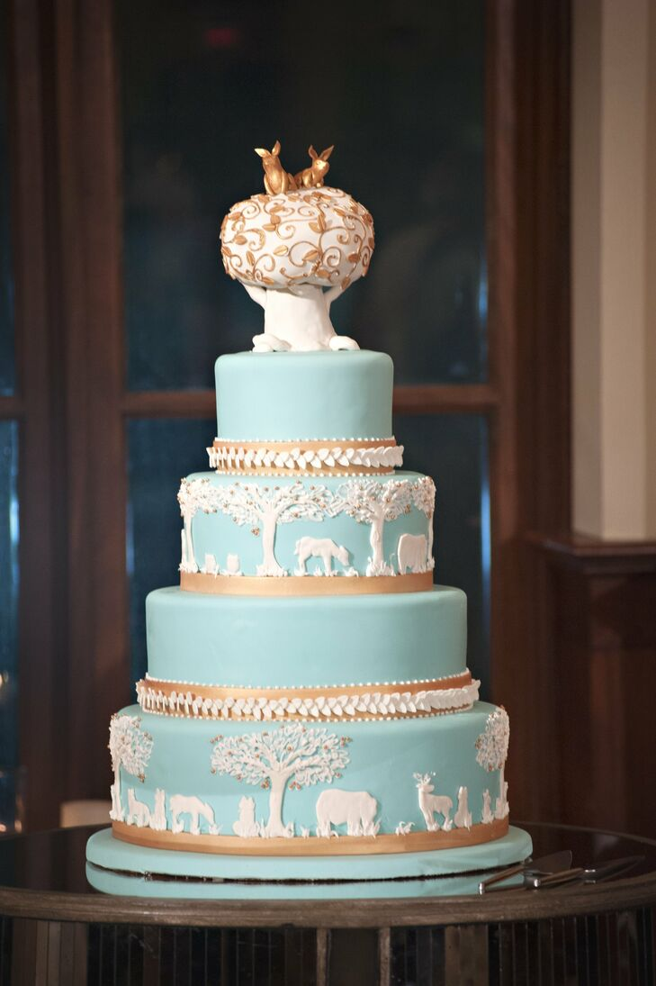 "The couple's unique animal motif cake was inspired by Wedgwood jasperware, which was popular in older, elegant homes, Abby explains. ""The topper—two bunnies on top of a giant tree— was adorable, and the whole thing was beyond all expectations,"" Abby says."