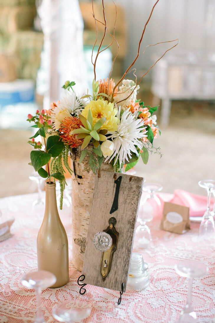 The tables' centerpieces were comprised of bright floral arrangements in birch vases and distressed wooden table numbers decorated with antique doorknobs and cast iron numbers.