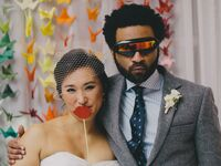 Couple posing with wedding photo booth props