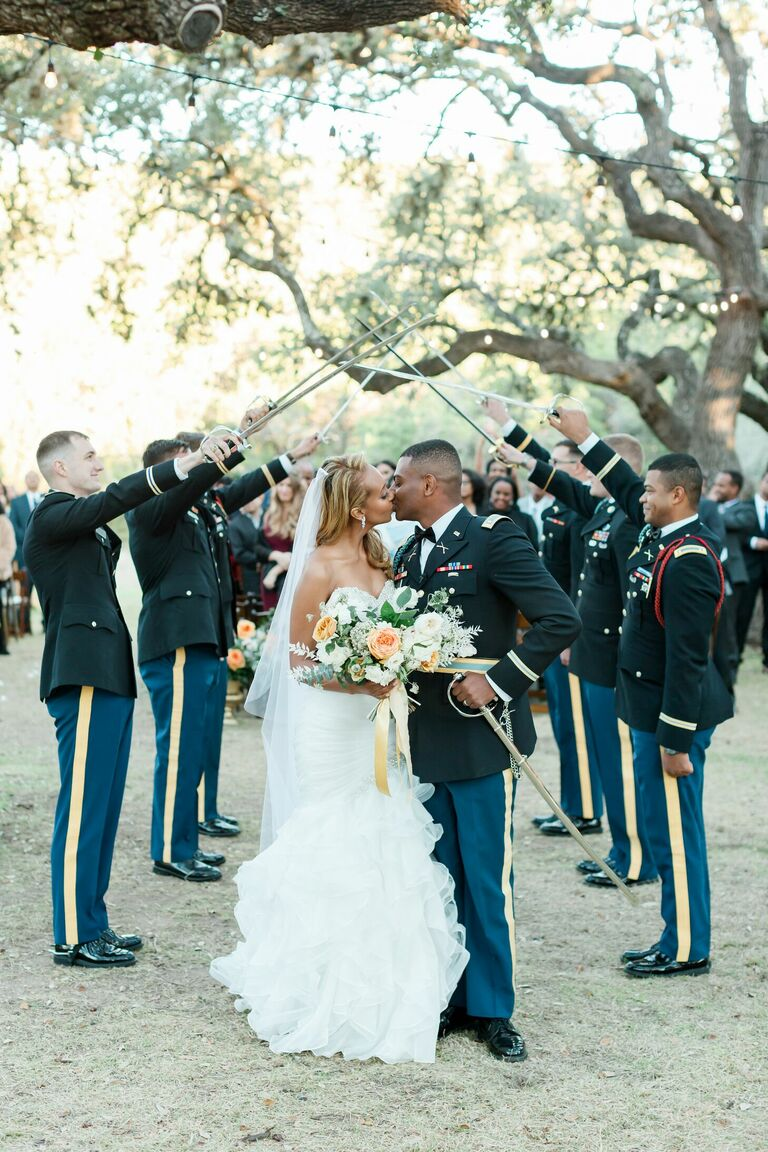 Couple kissing under military saber arch