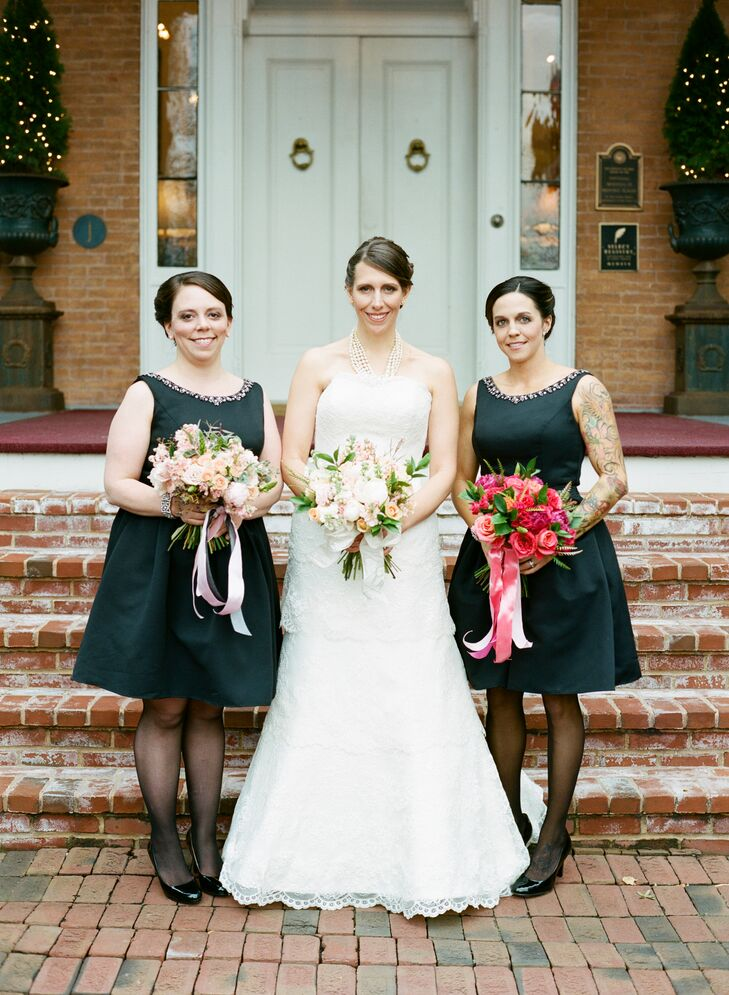 Jo's bridesmaids wore black, knee-length dresses in A-line silhouettes. They styled their hair up for the day.