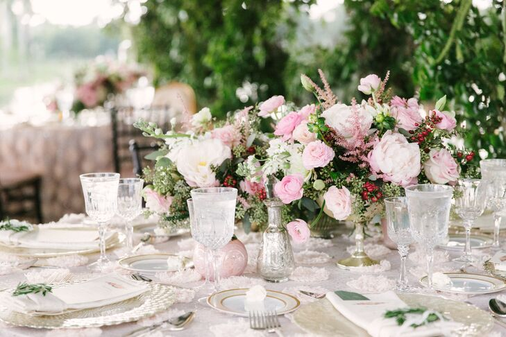 """Each round or family-style table included a lush arrangement of blush and cream ranunculus, roses, garden roses, peonies and lavender in mercury vases. Each was surrounded by silver accents and tealight candles. """"We wanted to give the feeling at each table of a garden tea party,"""" says Joyce."""