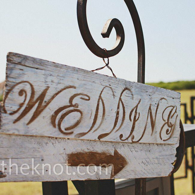 A rustic wood sign pointed guests to the ceremony.