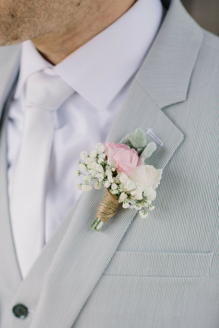 The groom wore a delicate pink and white rose and baby's breath boutonniere on the lapel of his light gray three-piece suit to match his white satin tie and the blush bridal bouquet.