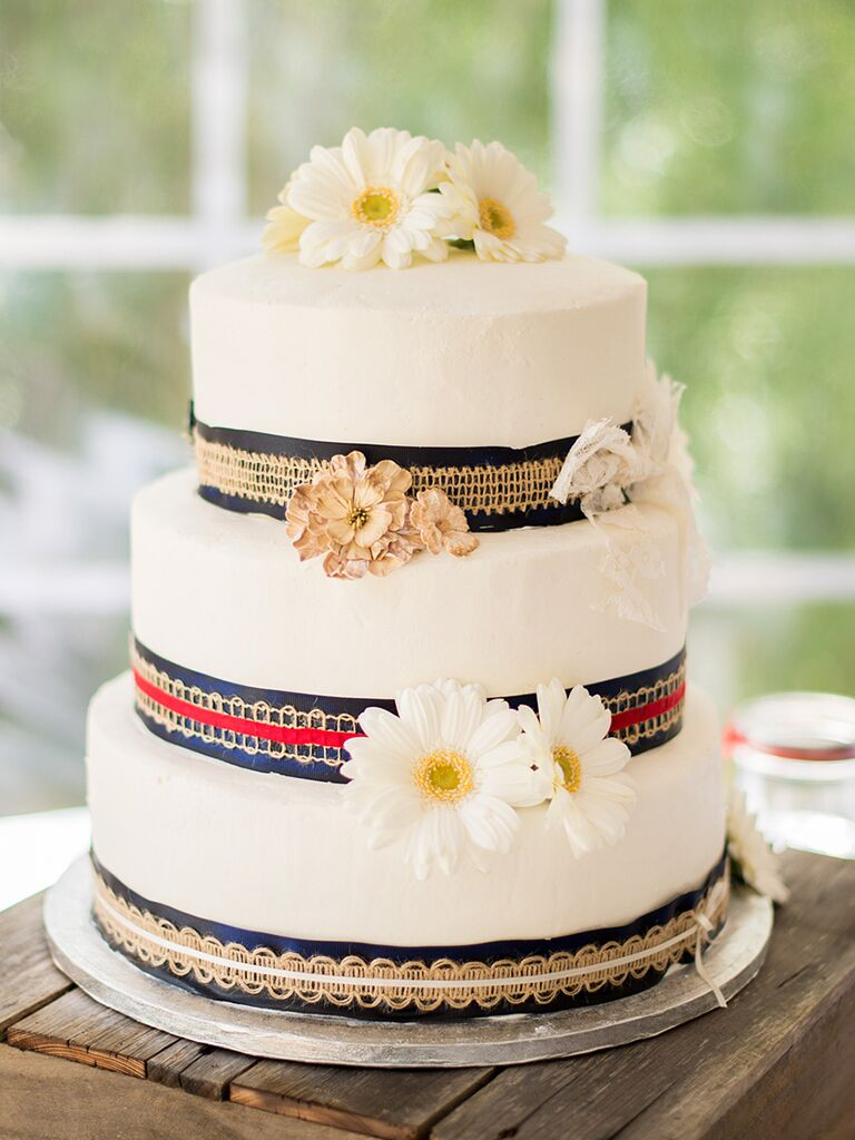 Rustic wedding cake with burlap ribbons and daisies
