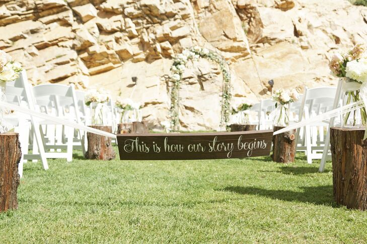 """Tree-trunk aisle decorations topped with blush and green floral arrangements in vases enhanced the romance for Ashlee and Dallan's outdoor ceremony at Louland Falls in Salt Lake City, Utah. A sign, which read """"This is how our story begins,"""" marked the aisle entrance before the ceremony began."""
