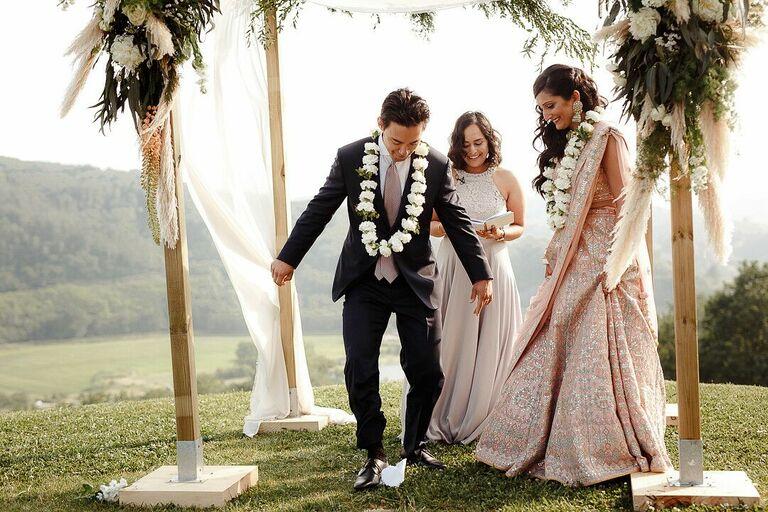 Groom breaking glass during outdoor wedding