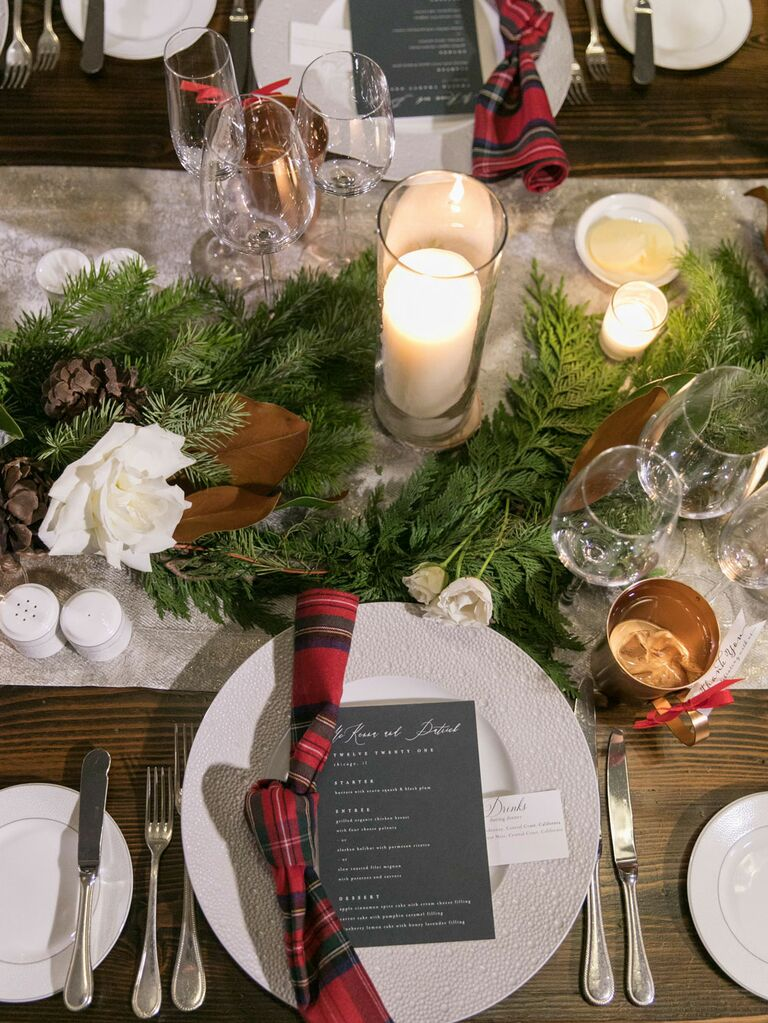 Christmas-inspired tablescape with plaid napkins and pine garland at winter wedding reception