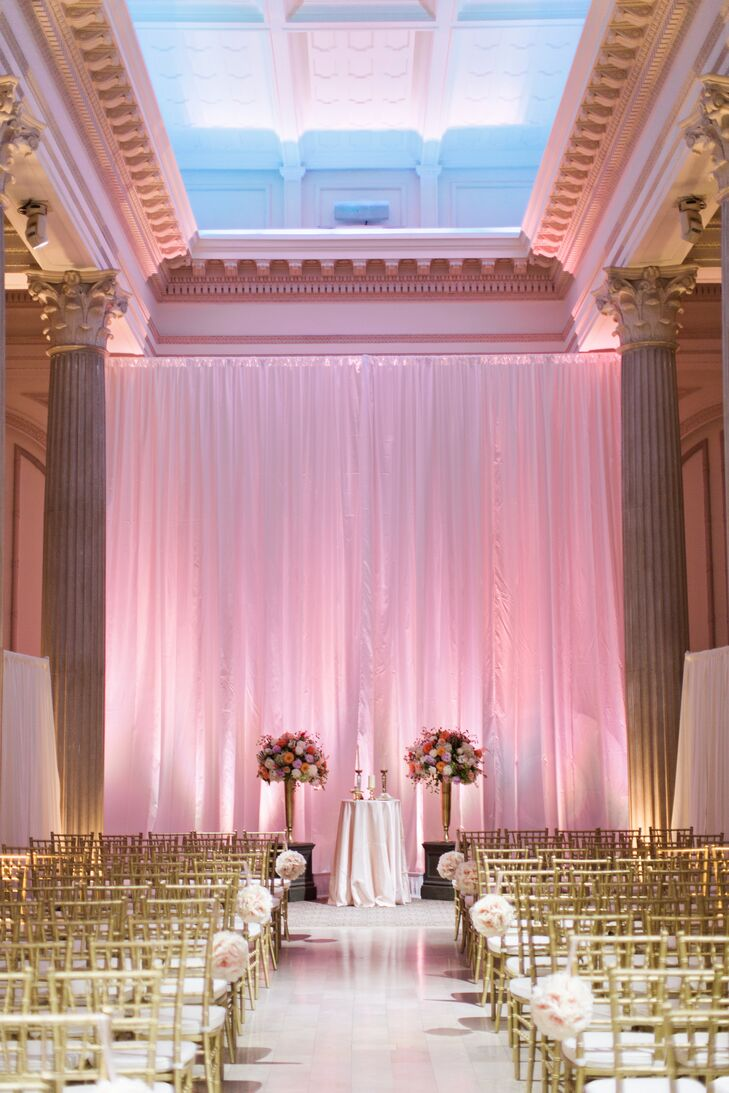 "For the ceremony, dramatic floor-to-ceiling silk draperies were illuminated with pink and white lights, giving the room a romantic glow. Two pedestals topped with floral arrangements flanked  a unity candle table. ""The bank's marble floors and tall white columns allowed for a magical entrance,"" Kellie says."