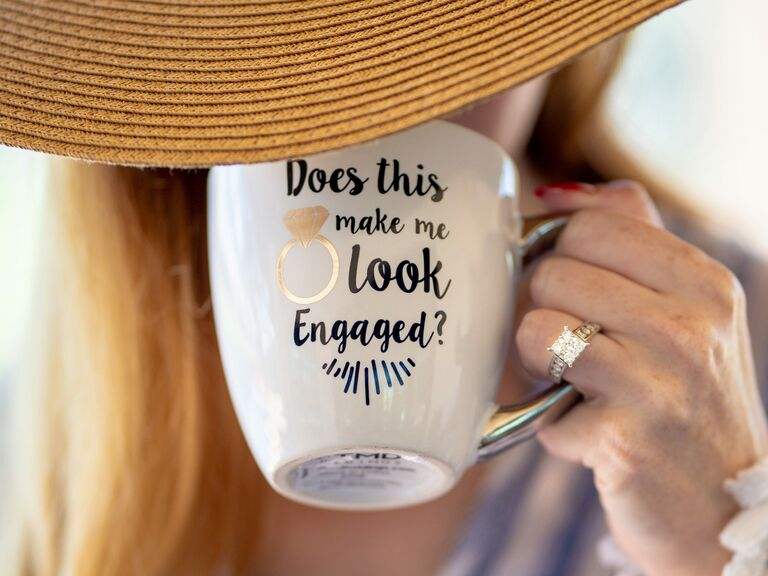 Engaged woman holding mug to show off engagement ring