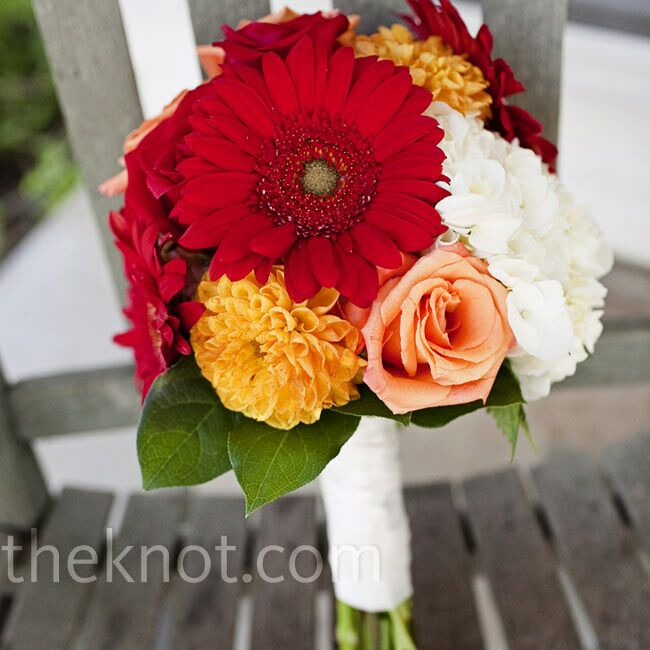 Jessica carried a bright mixture of red and peach roses, yellow dahlias, red gerbera daisies, and white hydrangeas tied with an ivory ribbon.
