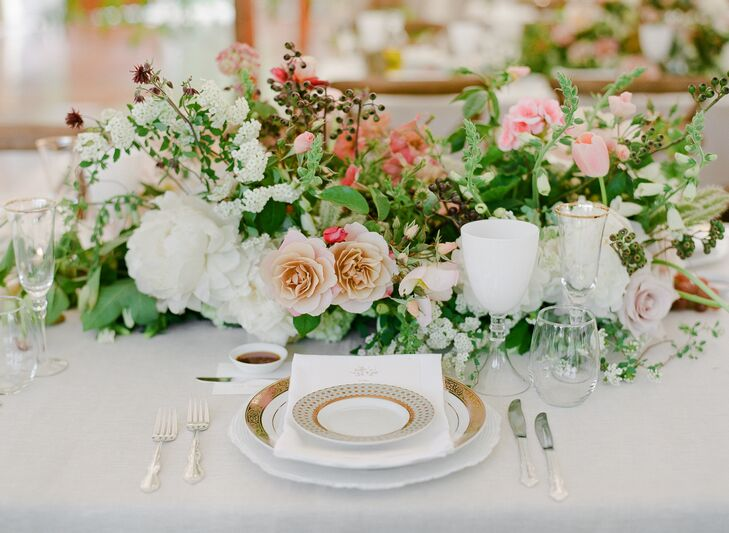 Gold rimmed china and glassware added a luxe touch to the whimsical, tented space. Centerpieces dotted with roses and TK filled the feasting tables.