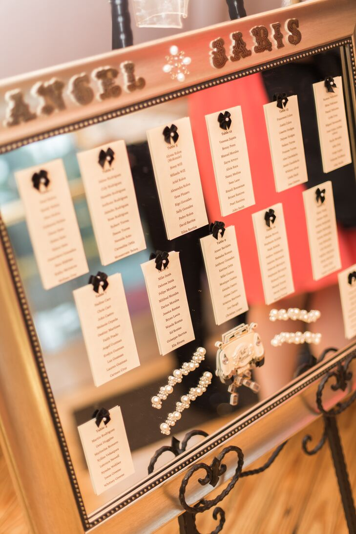 The couple's seating chart added a glamorous touch to the reception. All 140 guests found their names listed on a gold-framed mirror. Jaris and Angel's signature pearls marked the border and detailed each table card on a small black bow.
