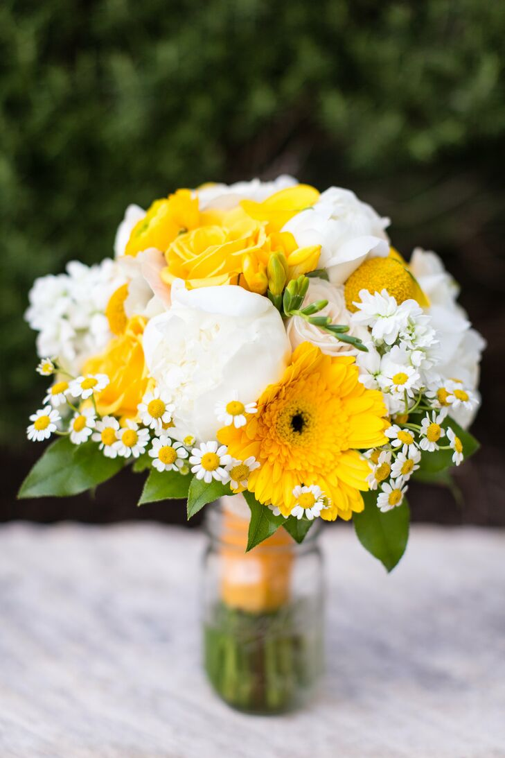 Bright yellow and white bouquets of Texas roses, gerbera daisies, peonies, billy balls and sunflowers complemented the bridesmaids' yellow dresses.