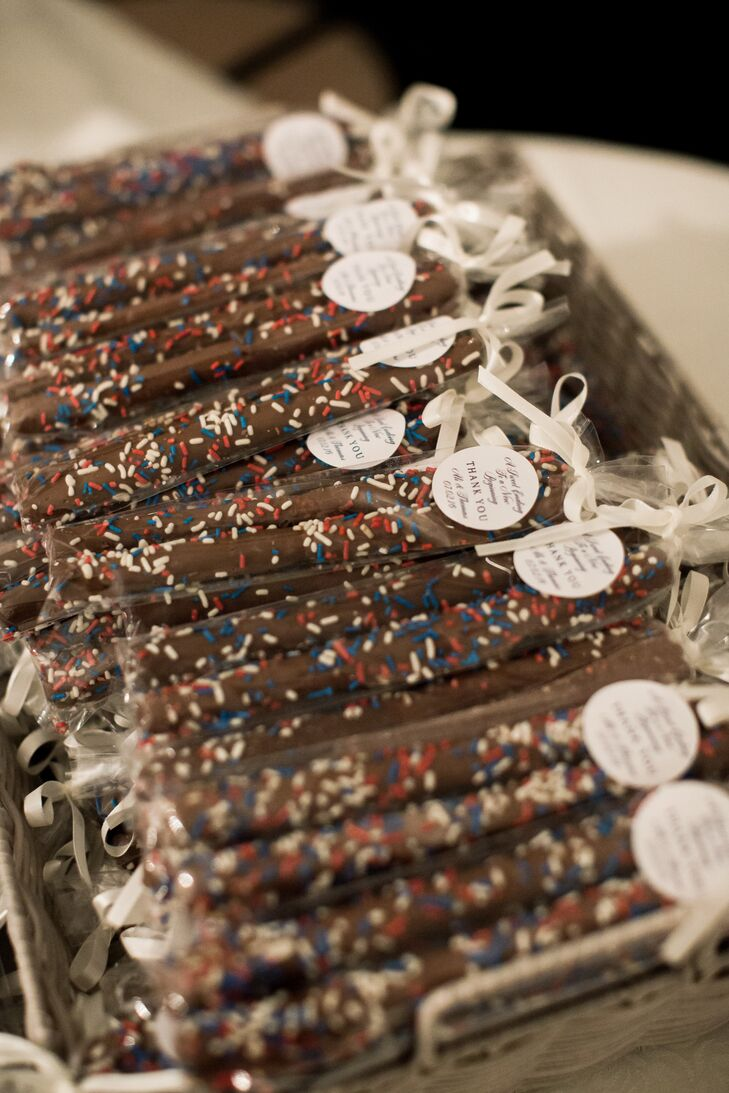 In celebration of the Fourth of July, Alexandra and Thomas treated their guests to chocolate covered pretzel sticks trimmed in ] red, white and blue sprinkles. The individually wrapped sweets were adorned with custom labels and white ribbons for a personalized feel.