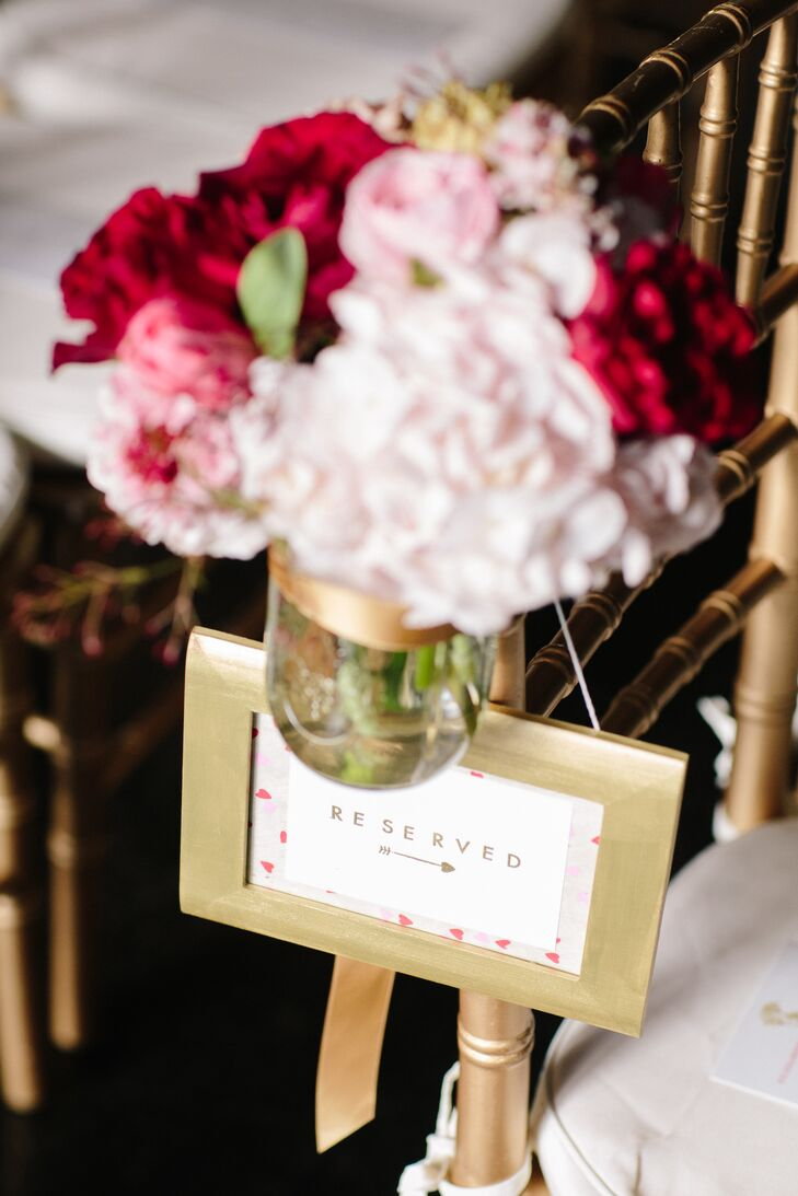 Simple gold frames popped against chiavari chairs in the same hue. For an added pop of color, red and pink arrangements of hydrangeas and garden roses lined the aisle.