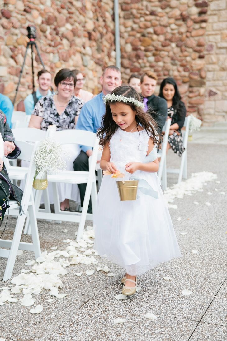 The flower girl carried a gold bucket, scattered petals down the aisle and wore a modified version of Brittany's gown. Guests received paper cones of rose petals to throw in the air—as the couple walked by—during the processional.
