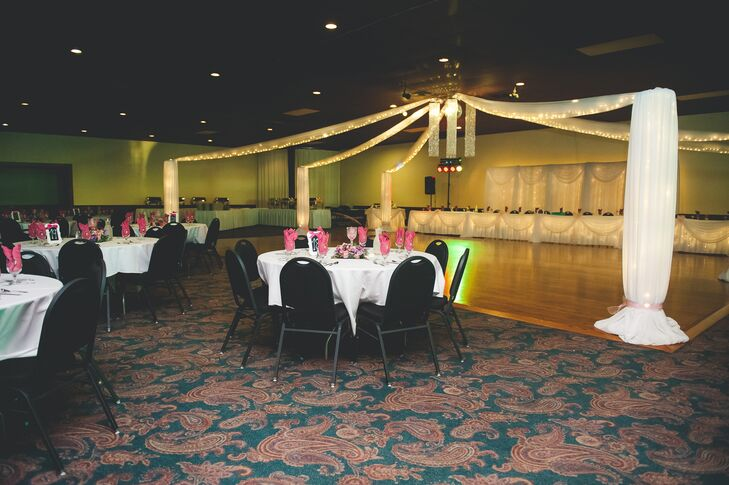 At the reception, white linens were draped from the ceiling lights above the dance floor. Round dining tables were dressed in white tablecloths with bright pink napkins.