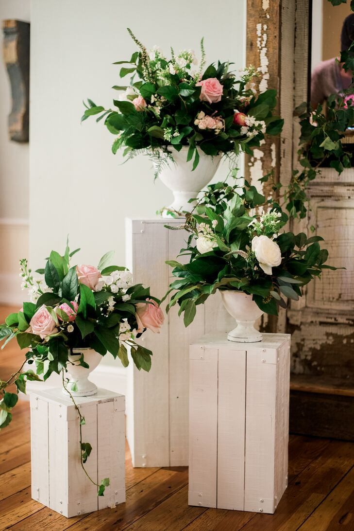 Flanking the altar, lush arrangements of greenery and blooms were placed on white rustic wooden pillars.
