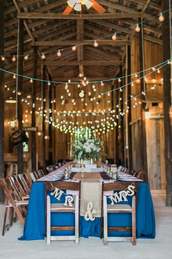 """The barn reception featured a long farmhouse dining table that was covered in navy linens, a burlap table runner and blush napkins. String lights hung above the table and the wooden folding chairs. Lauren and Daniel's seats were decorated in a gold """"Mr & Mrs"""" sign."""