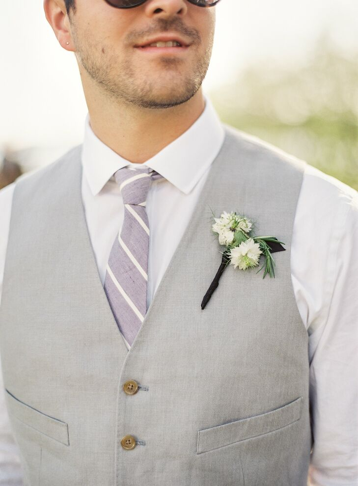 A striped purple tie and simple white boutonniere popped against the groomsmen's gray linen vests.