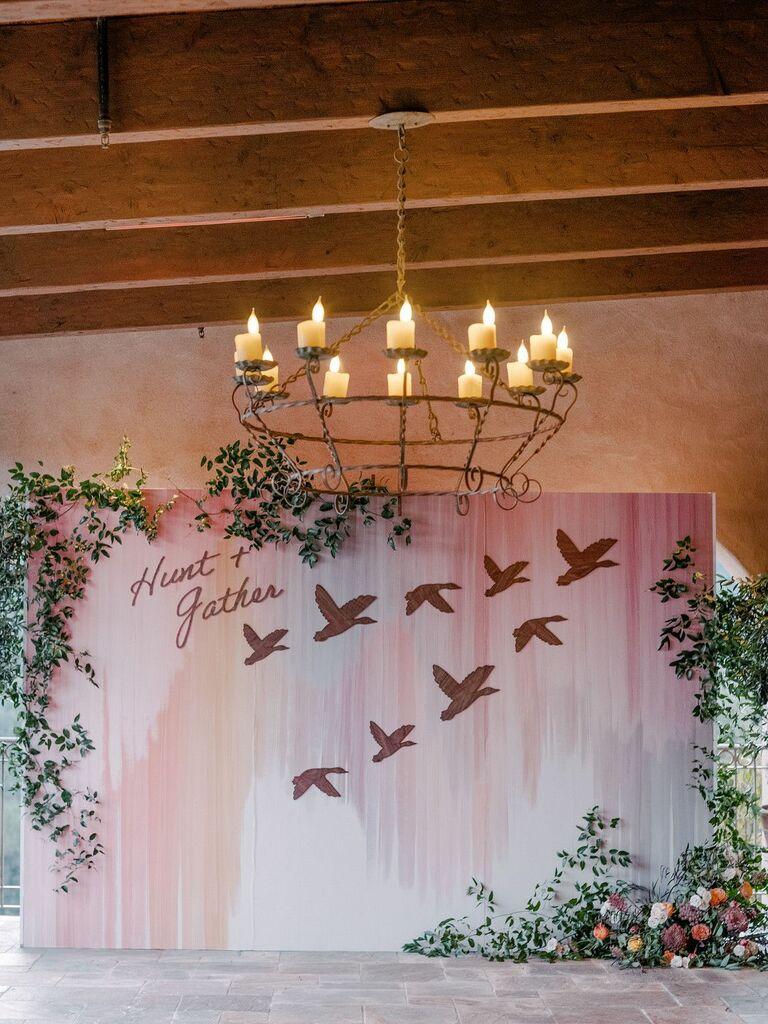 Pastel pink backdrop with bird details underneath chandelier