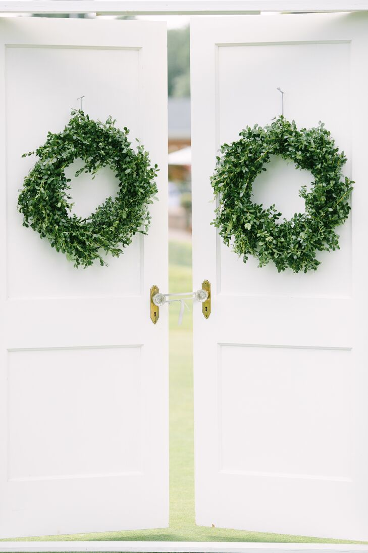 """Decor was chosen carefully for the ceremony, with the couple focusing on a handful of details that would make the most impact in the quaint outdoor space. """"I saw a pictured somewhere along the way of a wedding with French doors at the end of the aisle and had to have them,"""" says Lynn. """"I just really love the moment when the doors open and the bride and groom look at each other and I wanted to have that."""" With the help of her parents, Lynn was able to construct a frame with doors left over from a recent home renovation, which she decorated with boxwood wreaths for the ceremony."""