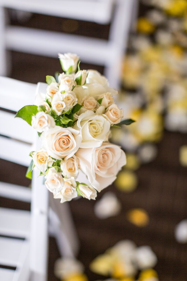 Clusters of blush and ivory roses decorated the ends of the chairs along the ceremony aisle.