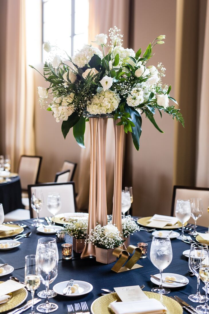 Three floral arrangements in different sizes created the reception centerpieces. Certain vases were spray-painted in gold to match the color scheme.