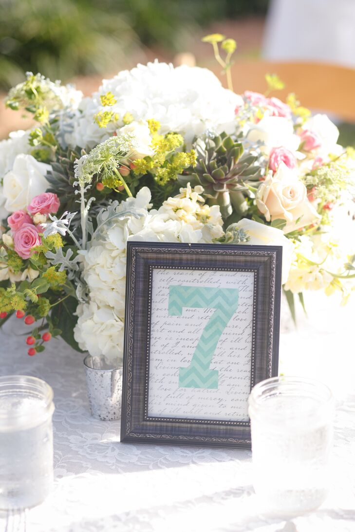 The couple decorated each round reception table with a chevron table number and lush floral centerpiece. Each arrangement included white hydrangea, blush roses, pink tea roses, succulents and dusty miller.