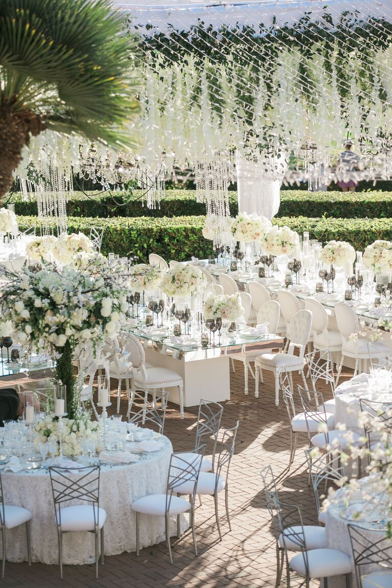 Glam outdoor wedding with hanging floral designs and dramatic tables capes