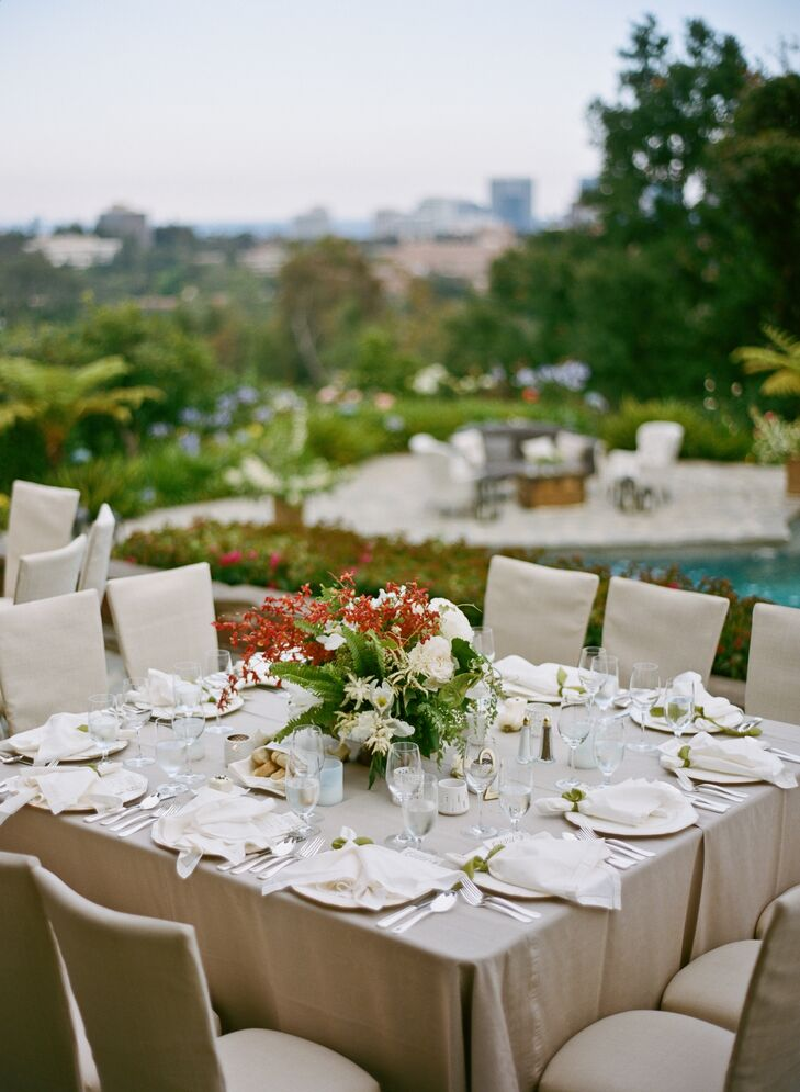 Neutral tablecloths and ceremony chairs made the pops of burnt orange orchids stand out all the more.