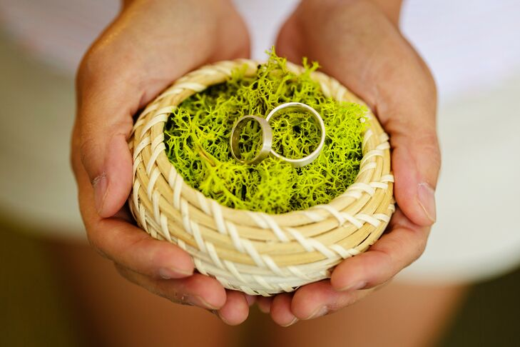 """Connie's wedding ring had a white gold band and Dan's wedding ring had a wide silver band, both engraved with """"You are loved."""" The rings were made by the Etsy online shop Aide-memoire Jewelry, and placed on top of reindeer moss."""