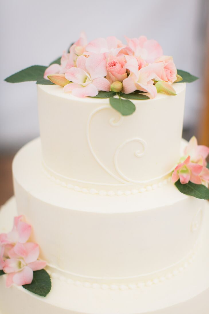 """The cake was probably the most important thing to my husband,"" Nicole says. The couple's simple white tiered cake was flavored orange pistachio and came from a Boston-area bakery."