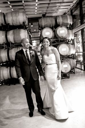 Couple Posing with Barrels of Wine at Winery Wedding