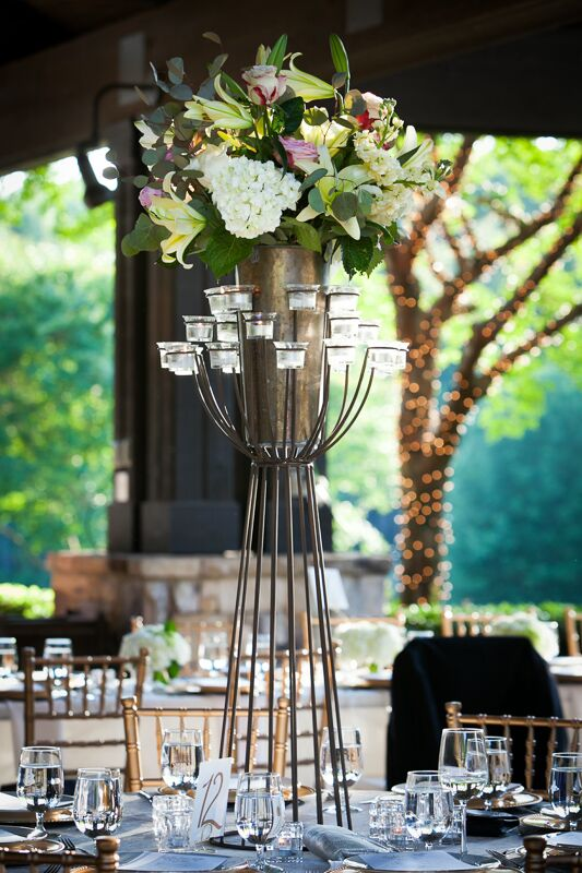 The reception tables were decorated with towering black iron candelabras to add a little dimension to the country club ballroom. The centerpieces were topped with ivory hydrangeas and lilies for an added touch of romance.