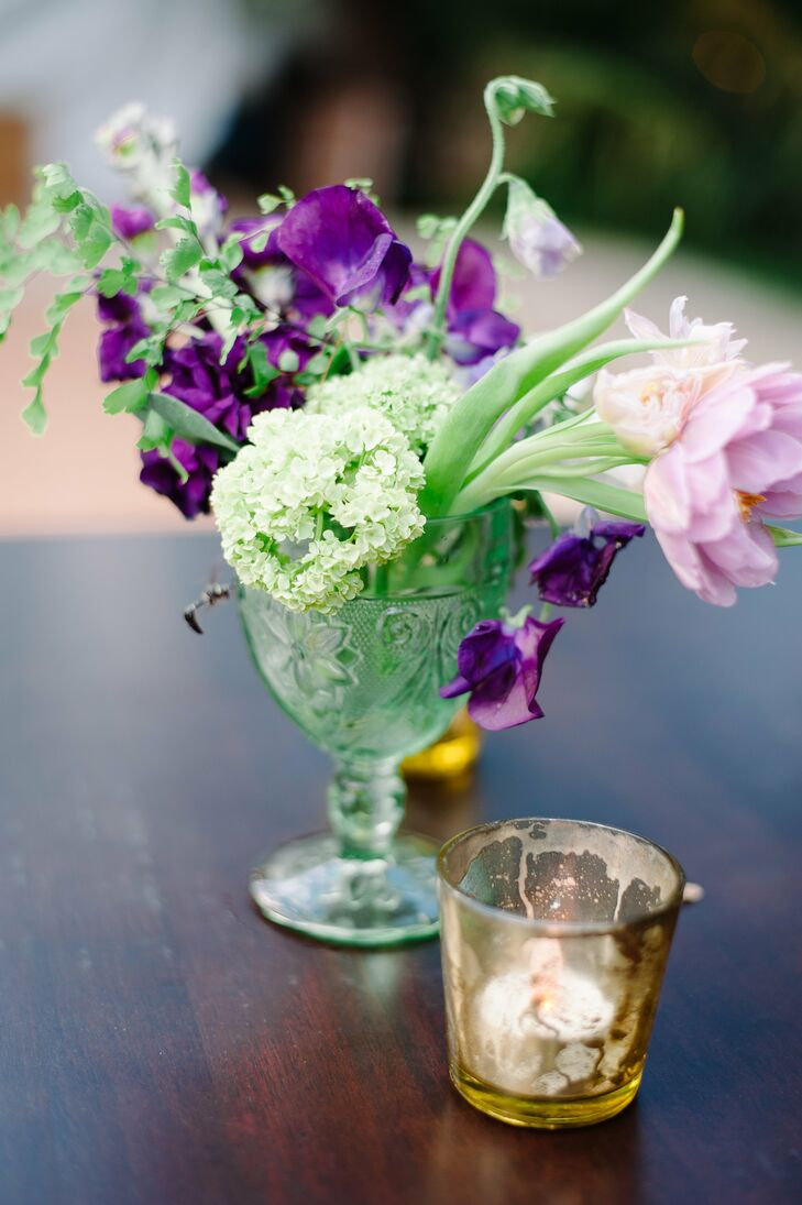 Vintage glasses and vases filled with flowers were used as centerpieces; mercury glass votives added sparkle.