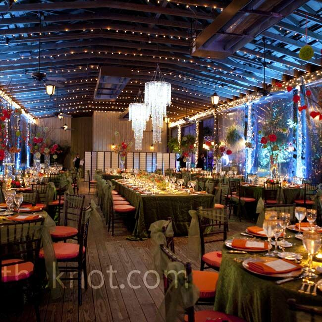The couple dined at a banquet table with their family in the center of the room beneath two chandeliers. Dramatic uplighting shifted from orange to blue as the  night progressed.
