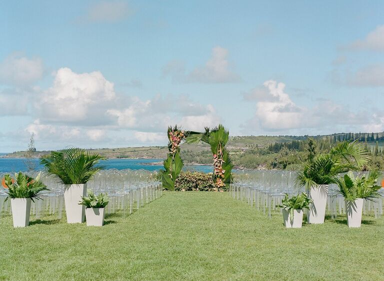 Waterfront wedding ceremony with ghost chairs and tropical leaf arch