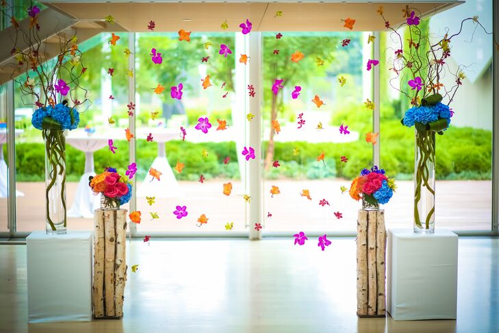 """""""My favorite element was our flower curtain,"""" Maria says. The breathtaking ceremony backdrop included blue hydrangeas and hot pink, orange, red and green orchid blossoms to brighten the monochromatic modern space."""