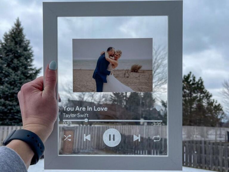 Woman holding up framed glass plaque of Taylor Swift song You Are In Love with picture of couple on their wedding day