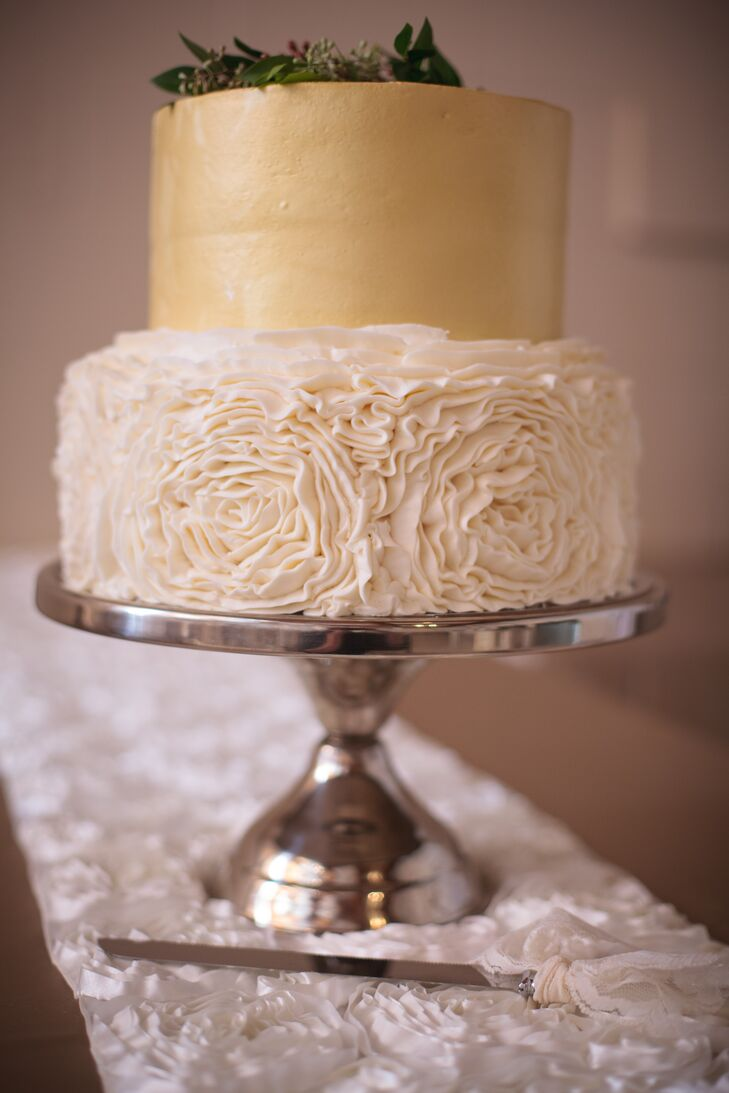 The two tier cake had a bottom layer of white rose pattered frosting and a top layer of gold frosted fondant.