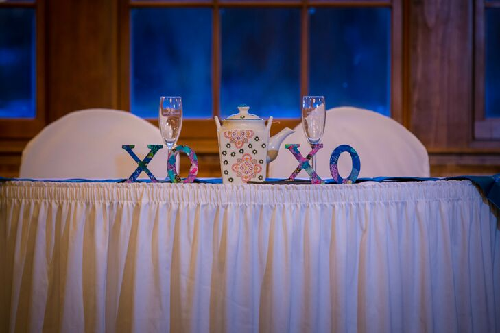 "A teapot and ""XOXO"" letters decorated the couple's head table in lieu of floral arrangements."